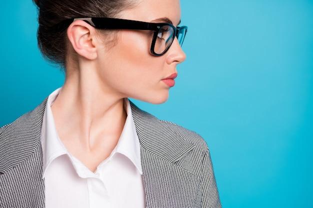 Beschnittenes nahaufnahmeprofil-seitenansichtsporträt einer attraktiven fokussierten direktorin, die beiseite kopienraum einzeln auf hellblauem farbhintergrund schaut