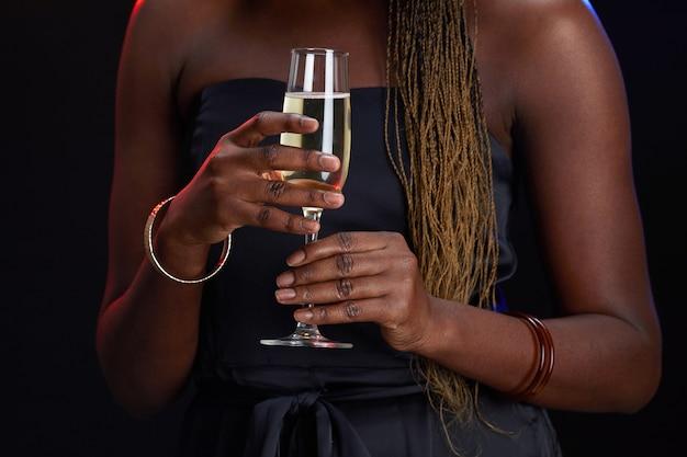Beschnittenes porträt der eleganten afroamerikanischen frau, die champagnerglas hält, während party-, kopienraum genießt