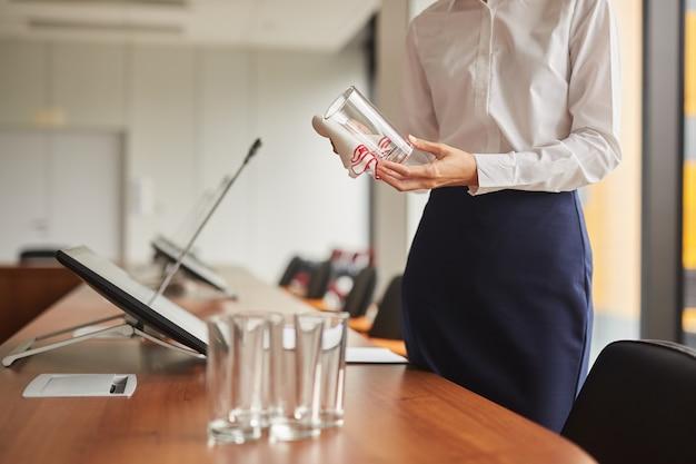 Beschnittenes porträt der nicht erkennbaren weiblichen assistentin, die glas abwischt, während konferenzraum für geschäftsereignis vorbereitet,