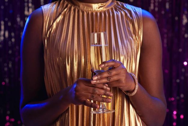 Beschnittenes porträt der nicht wiedererkennbaren afroamerikanischen frau, die champagnerglas hält, während party genießen, raum kopieren