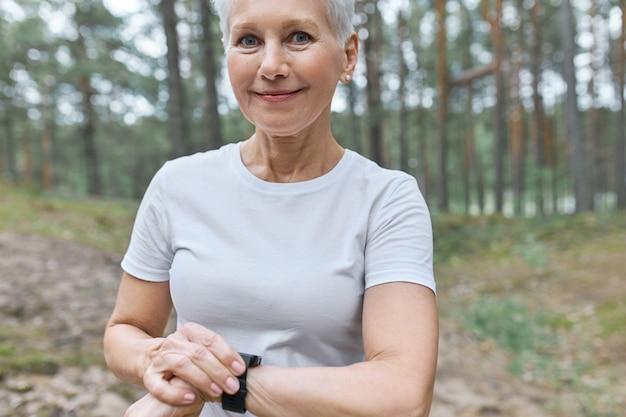 Beschnittenes porträt der schönen frau mittleren alters im weißen t-shirt, das intelligente uhr an ihrem handgelenk anpasst