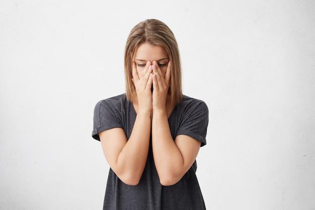 Beschnittenes porträt der traurigen müden frau, die gesicht mit händen bedeckt, die augen voller schmerz und stress haben, die müdigkeit haben. stressvolle schöne frau, die panik hat, die versucht, sich zu konzentrieren und lösung zu finden.