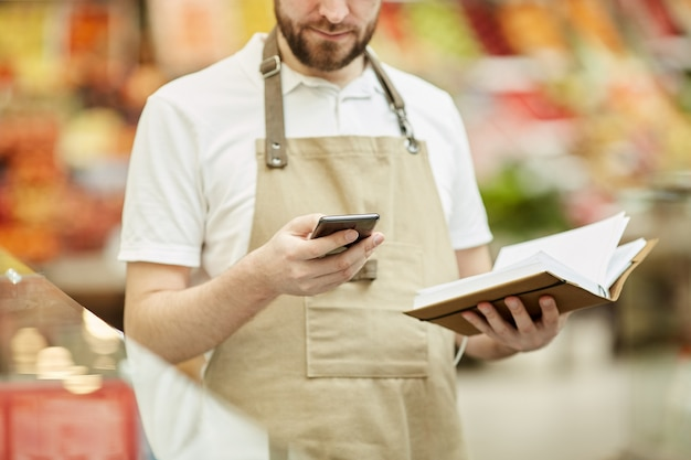 Beschnittenes porträt des bärtigen mannes, der durch smartphone anruft, während inventarzählung im supermarkt tut