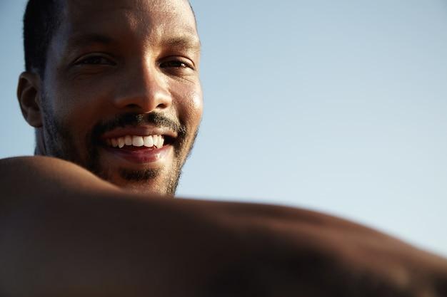 Beschnittenes porträt des freudigen jungen afrikanischen mannes mit kleinem bart, der auf pflaster sitzt und sonniges wetter genießt, lächelnd