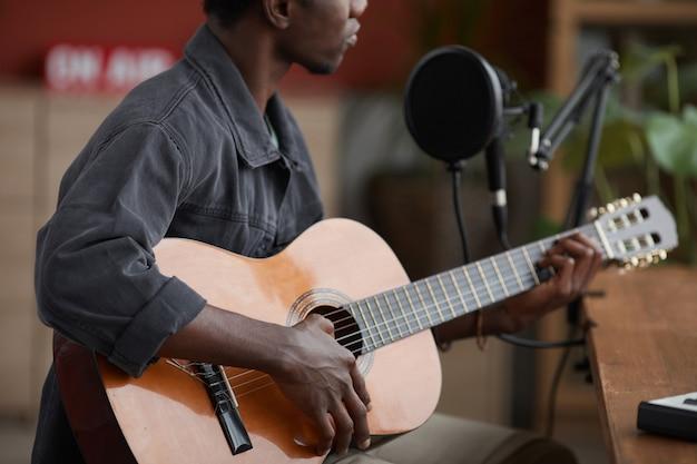 Beschnittenes porträt des jungen afroamerikanischen mannes, der gitarre spielt, während er durch mikrofon im hauptaufnahmestudio sitzt, raum kopiert