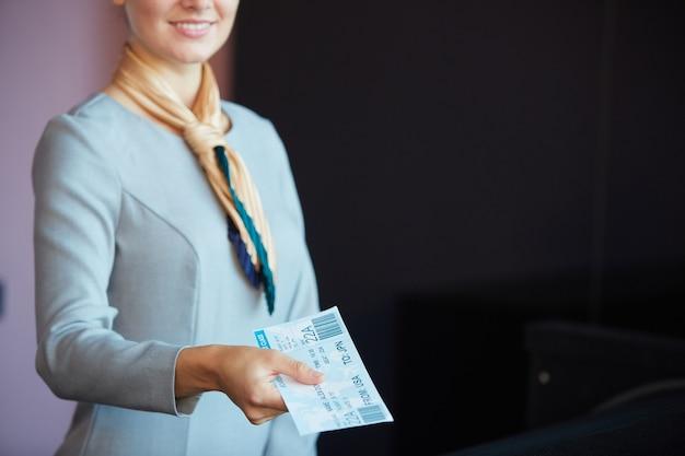 Beschnittenes porträt des lächelnden flugbegleiters, der dem passagier tickets gibt, während er am check-in-schalter im flughafen steht