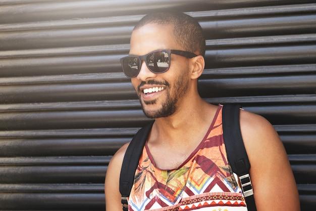 Beschnittenes porträt des lächelnden gutaussehenden afroamerikanischen mannes, der sonnenbrillen trägt, die gegen schwarze wand stehen