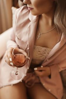 Beschnittenes porträt einer jungen frau, die im sessel sitzt und ein glas wein in ihrer hand hält. konzept luxus lifestyle