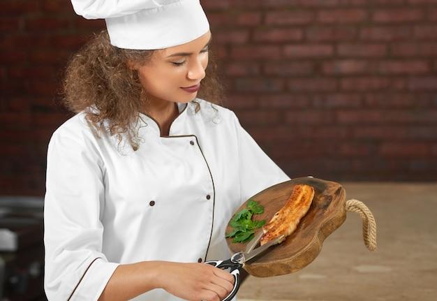 Beschnittenes porträt einer schönen professionellen köchin, die im restaurant kocht, das gegrilltes fleisch mit scheren-copyspace schneidet.