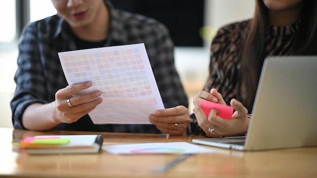 Beschnittenes schussgrafikdesign, das sie projekt auf tisch mit laptop treffen.