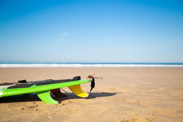 Beschnittenes surfbrett oder longboard am sandstrand liegend