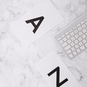 Beschriften sie a und z auf weißbuch und tastatur auf strukturiertem hintergrund des weißen marmors