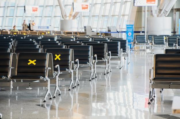 Beschriftete wartestühle für soziale distanzierung an einem flughafen