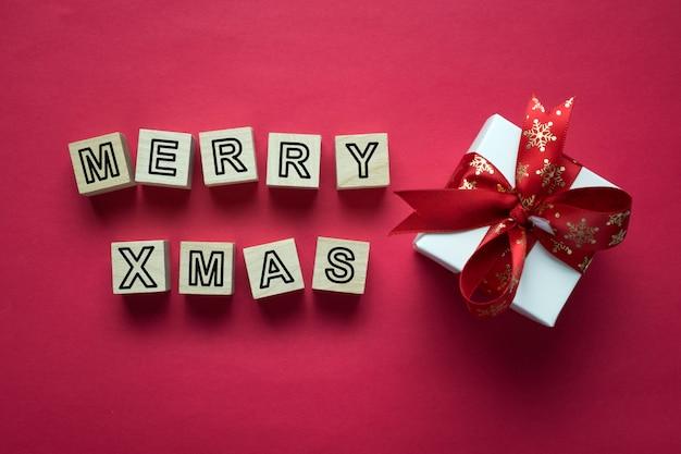 Beschriftung der frohen weihnachten mit feiertagsgrußgeschenk