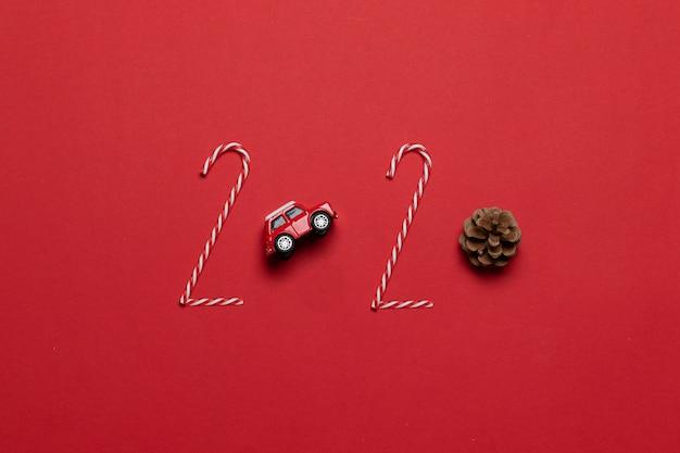 Beschriftung des weihnachts- und neujahrsfeiertags 2020 des roten autospielzeugs der verschiedenen dekoration, tannenzapfen auf einem roten hintergrund