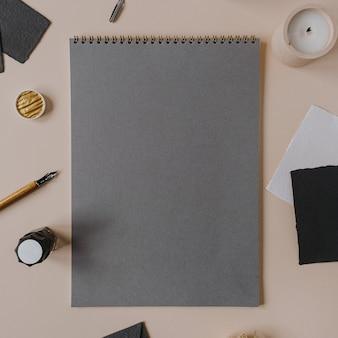 Beschriftung, handschriftkonzept mit leerem leeren papierblatt-spiralblock, stift, tinte, briefpapier auf beige. flach liegen