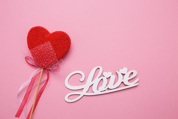 Beschriftung von holzbuchstaben lieben auf einem rosa isolierten hintergrund. herz in form von süßigkeiten am stiel.