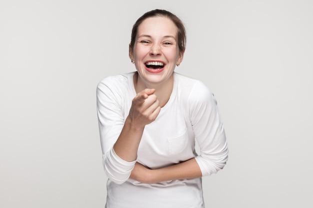 Beschuldige dich oder beschäme dich. mädchen, das auf kamera zeigt und lächelt. studioaufnahme, grauer hintergrund