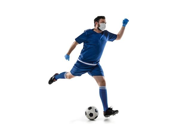 Besiege die krankheit. männlicher fußball, fußballspieler in schutzmaske. auch während der quarantäne aktiv. gesundheitswesen, medizin, sportkonzept.