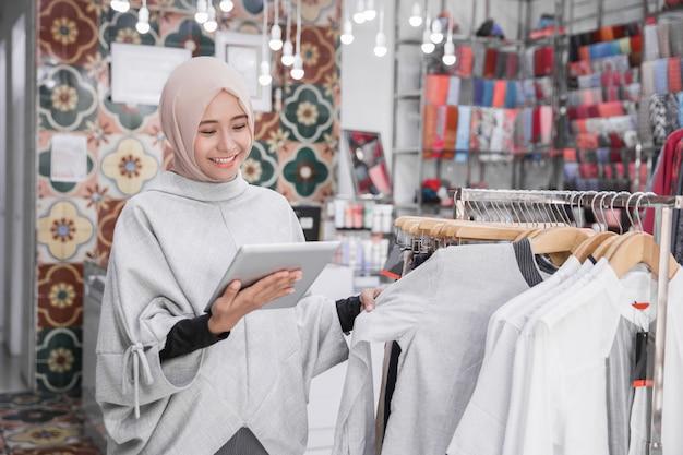 Besitzer einer muslimischen modeboutique mit tablet-checking-bestand