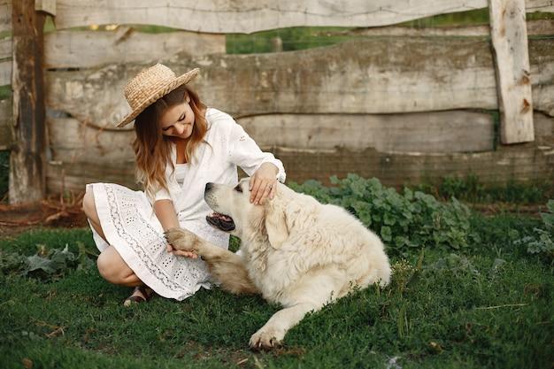 Besitzer und labrador retriever hund in einem hof. frau in einem weißen kleid. golden retriever.