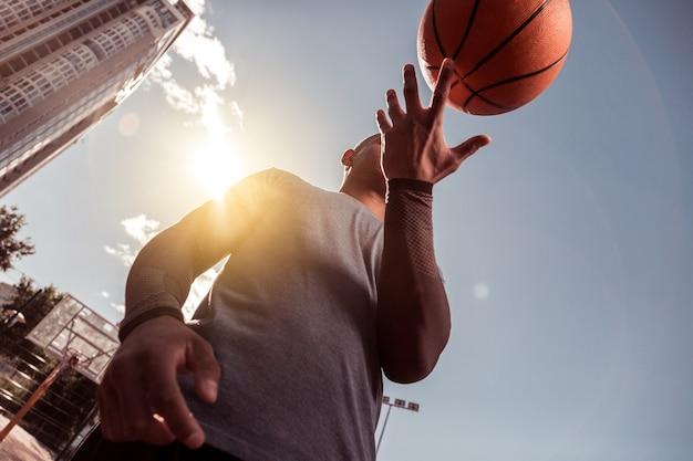 Besondere fähigkeiten. niedriger winkel eines netten mannes, der einen ball auf seinem finger hält, während er ihn dreht
