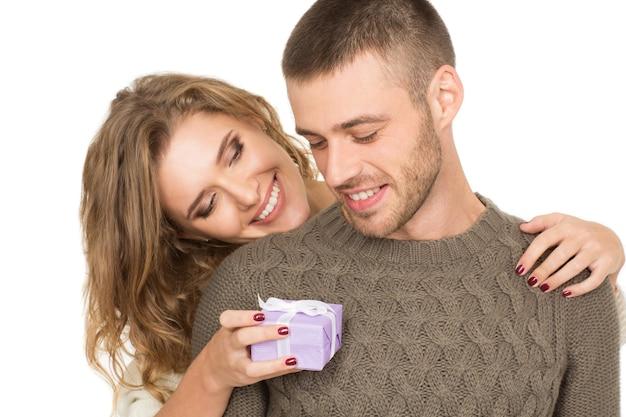 Besondere person. glückliche liebende freundin, die ihren mann umarmt und ihm eine kleine geschenkbox gibt