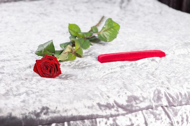 Besonderes romantisches valentinstagsgeschenk mit einer einzelnen langstieligen roten rose und einem roten geschenk in geschenkverpackung, das auf dem bett auf der weißen tagesdecke liegt