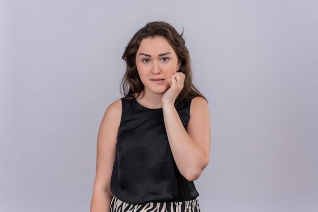 Besorgniserregendes kaukasisches junges mädchen, das schwarze unterhemdkratzbacke auf weißem hintergrund trägt