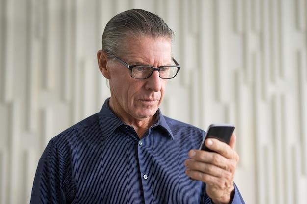 Besorgt alter mann lesetext-meldung am telefon