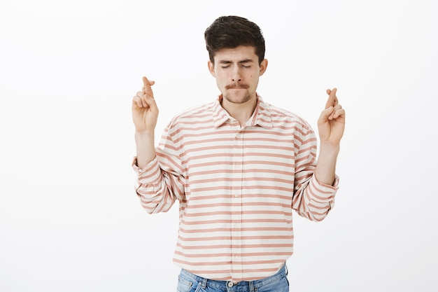 Besorgt fokussiert attraktiver bärtiger kerl in gestreiftem hemd, hob gekreuzte hände und schloss die augen, saugte die lippen vor nervosität, hoffte oder wünschte, betete gott um glück über graue wand