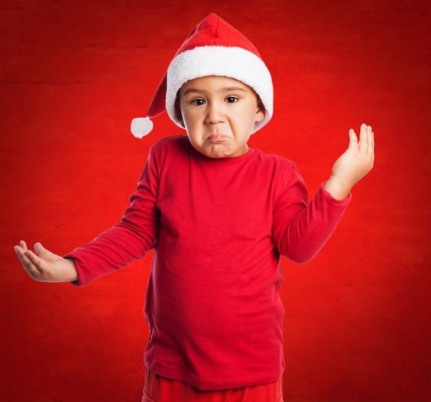 Besorgt kind tragen weihnachtsmann-hut