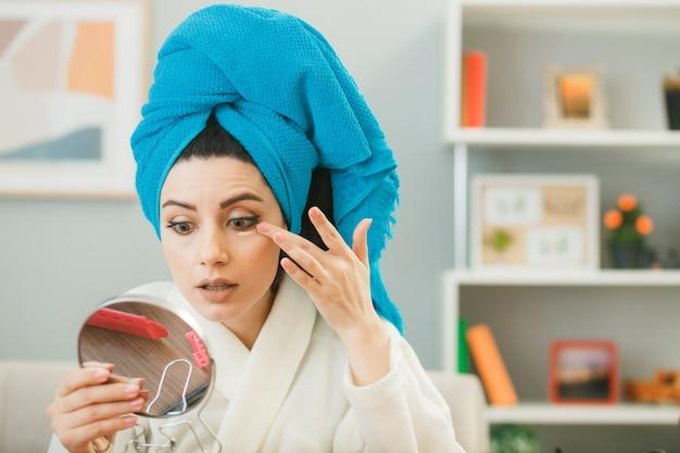 Besorgt mit blick auf den spiegel junges mädchen, das mit ton-up-creme eingewickeltes haar in ein handtuch aufträgt, das am tisch mit make-up-tools im wohnzimmer sitzt?