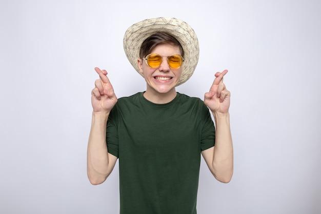 Besorgt mit geschlossenen augen, die die finger kreuzen, junger gutaussehender kerl, der hut mit brille trägt