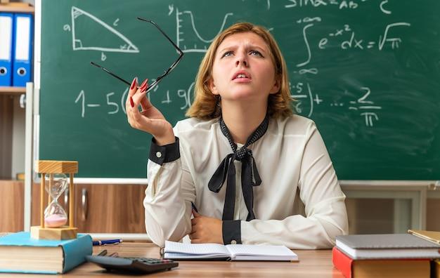 Besorgt nachschlagen junge lehrerin sitzt am tisch mit schulwerkzeugen mit brille im klassenzimmer Kostenlose Fotos