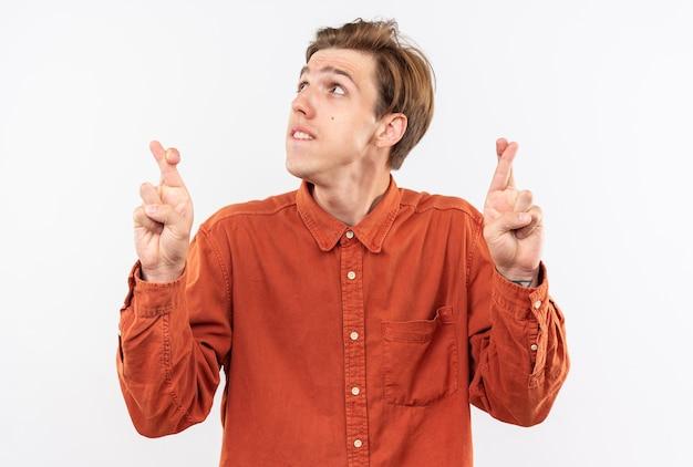 Besorgt nachschlagen junger gutaussehender kerl mit rotem hemd, das die finger isoliert auf weißer wand kreuzt