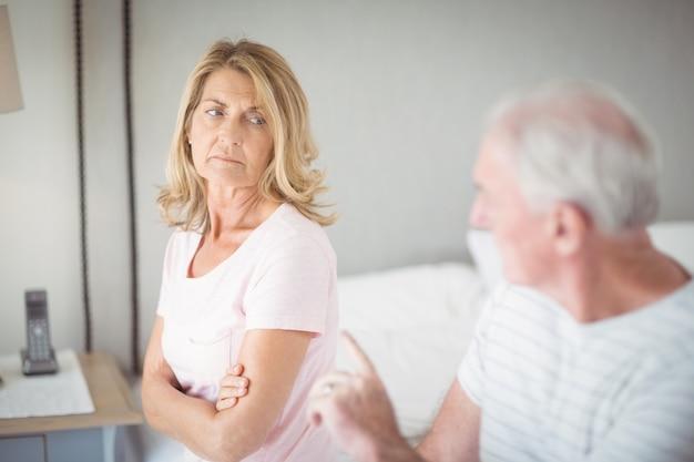 Besorgte ältere frau, die auf bett sitzt