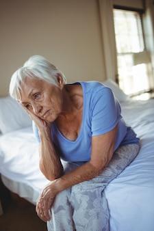 Besorgte ältere frau, die auf dem bett im schlafzimmer zu hause sitzt