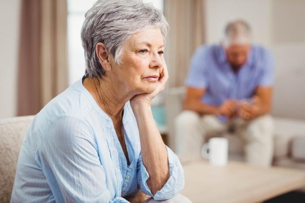 Besorgte ältere frau, die auf sofa im wohnzimmer sitzt