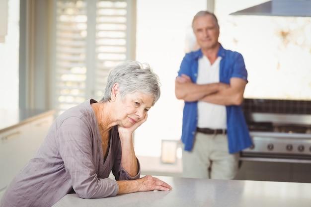 Besorgte ältere frau, die mit mannstellung sitzt