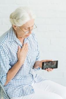 Besorgte ältere frau, die smartphone mit defektem bildschirm gegen weiße wand betrachtet