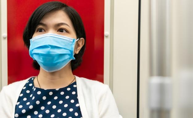 Besorgte asiatische frau tragen chirurgische maske in der u-bahn
