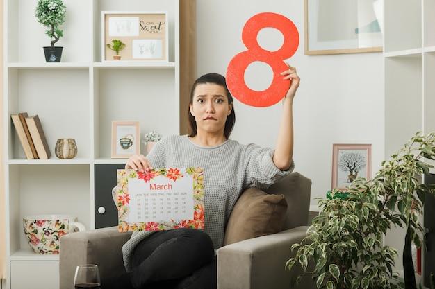 Besorgte beißt lippen, die ein schönes mädchen an einem glücklichen frauentag aussehen, der die nummer acht mit dem kalender hält, der auf einem sessel im wohnzimmer sitzt
