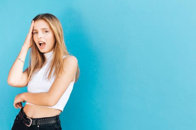 Besorgte blonde junge frau gegen blauen hintergrund