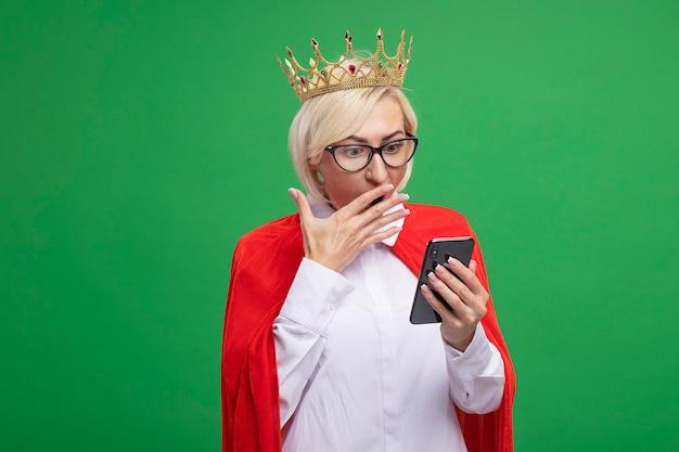 Besorgte blonde superheldin mittleren alters in rotem umhang mit brille und krone, die das handy hält und betrachtet, das die hand auf dem mund hält, isoliert auf grüner wand mit kopierraum