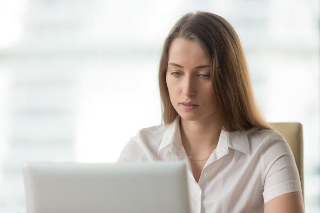 Besorgte ernste geschäftsfrau, die an der laptop-computer, schirm betrachtend arbeitet