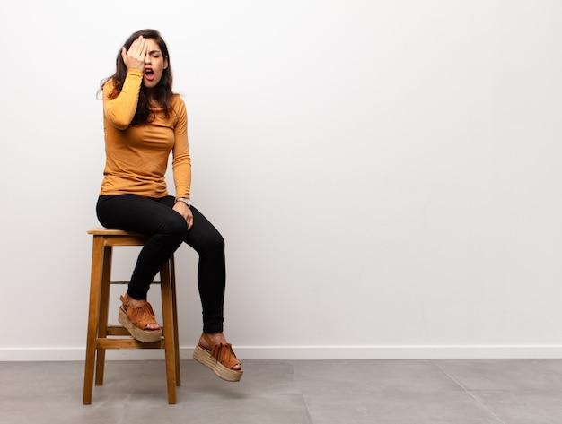 Besorgte frau auf stuhl, gesichtspalmengeste