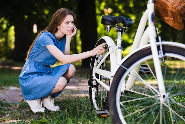 Besorgte frau, die ihr fahrrad überprüft