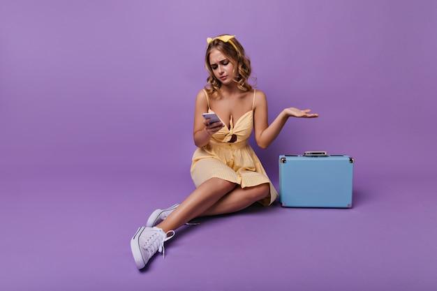 Besorgte frau, die mit telefon auf dem boden sitzt. weiblicher reisender, der neben koffer aufwirft.