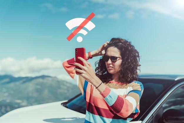 Besorgte frau, die nach autopanne signal sucht. sie hält ein rotes handy ohne signalsymbol. sie trägt ein buntes kratztrikot.